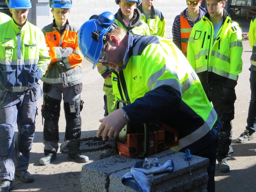 Jari antamassa moottorisaha koulutusta Vantaan Varian rakennusalan opiskelijoille.